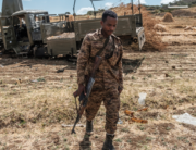 A member of the Ethiopian Defense Forces walks away from a damaged military truck abandoned on a road near the village of Ayasu Gebriel, East of the Ethiopian city of Alamata, on December 10, 2020. EDUARDO SOTERAS / AFP