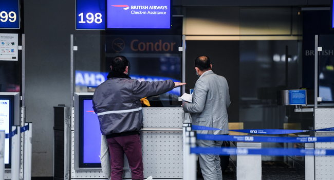 Passengers stand at the check-in of British Airways for a flight to London at Duesseldorf Airport in Duesseldorf, western Germany, on December 21, 2020, amid the ongoing novel coronavirus / COVID-19 pandemic. Ina FASSBENDER / AFP