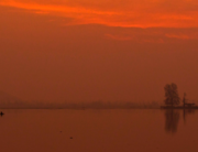 Men ride a boat in the waters of Dal Lake during the sunset in Srinagar on December 25, 2020. Tauseef MUSTAFA / AFP