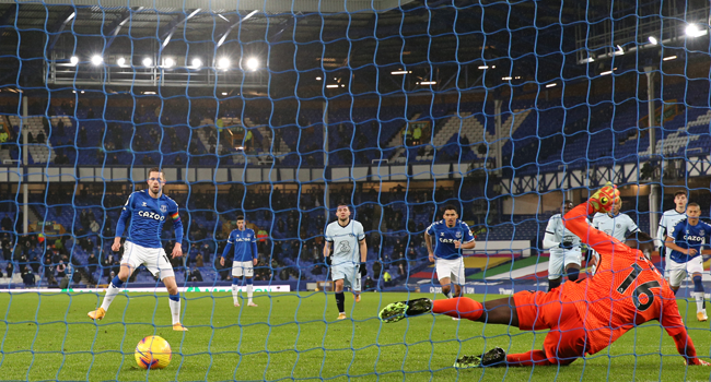 Everton's Icelandic midfielder Gylfi Sigurdsson (L) scores the opening goal from the penalty spot as Chelsea's French goalkeeper Edouard Mendy (R) dives the wrong way during the English Premier League football match between Everton and Chelsea at Goodison Park in Liverpool, north west England on December 12, 2020. Clive Brunskill / POOL / AFP