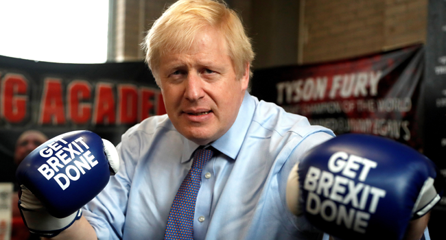 "In this file photo taken on November 19, 2019 Britain's Prime Minister and leader of the Conservative Party, Boris Johnson wears boxing gloves emblazoned with ""Get Brexit Done"" as he poses for a photograph at Jimmy Egan's Boxing Academy in Manchester north-west England on November 19, 2019, during a general election campaign trip. Frank Augstein / POOL / AFP"