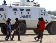 Sudanese children walk past an armoured vehicle of the United Nations and African Union peacekeeping mission (UNAMID) in Kalma Camp for internally displaced people in Nyala, the capital of South Darfur, on December 30, 2020.