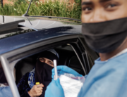A woman sits in her car before receiving a COVID-19 swab test by a Lab Technician from the Mullah Laboratories at the Flower Hall parking, at Wits University, Braamfontein, Johannesburg, during a drive through COVID-19 swab test campaign, on January 5, 2021. Luca Sola / AFP