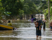 Residents walk along a road submerged by floodwaters in Mentakab in Malaysia's Pahang state on January 8, 2021, following heavy monsoon rains. Mohd RASFAN / AFP