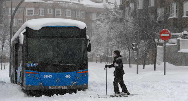 A woman skis past a bus stuck in a street amid a heavy snowfall in Madrid on January 9, 2021. PIERRE-PHILIPPE MARCOU / AFP