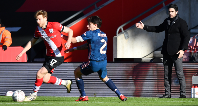 Arsenal's Spanish manager Mikel Arteta (R) watches as Southampton's Scottish midfielder Stuart Armstrong (L) vies with Arsenal's Spanish defender Hector Bellerin during the English FA Cup fourth round football match between Southampton and Arsenal at St Mary's Stadium in Southampton, Hampshire,on January 23, 2021. Ben STANSALL / AFP