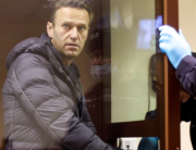 This screen grab from a handout footage provided by the Babushkinsky district court on February 5, 2021, shows Russian opposition leader Alexei Navalny, charged with defaming a World War II veteran, looking from inside a glass cell during a court hearing in Moscow. Handout / Moscow's Babushkinsky district court press service / AFP