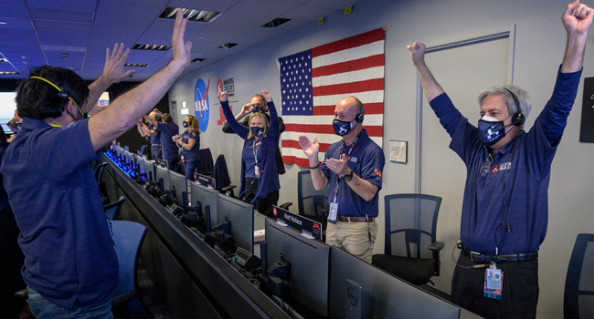 This NASA photo shows members of NASA's Perseverance rover team as they react in mission control after receiving confirmation the spacecraft successfully touched down on Mars, on February 18, 2021, at NASA's Jet Propulsion Laboratory in Pasadena, California.   Bill INGALLS / NASA / AFP