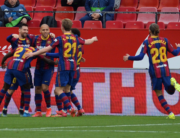 Barcelona's Argentinian forward Lionel Messi (L) celebtates with teammates after scoring during the Spanish league football match between Sevilla FC and FC Barcelona at the Ramon Sanchez Pizjuan stadium in Seville on February 27, 2021. CRISTINA QUICLER / AFP