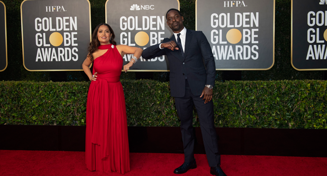 This handout photo courtesy of the HFPA shows Salma Hayek and Sterling K. Brown elbow bump as they arriving for the 78th Annual Golden Globe Awards in Beverly Hills, California on February 28, 2021.  HFPA / AFP