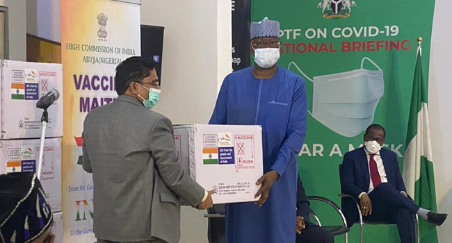 Chairman of the Presidential Task Force on COVID-19, Boss Mustapha, receives a box of vaccine from a representative of the Indian government on April 6, 2021.