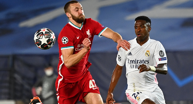 Liverpool's English defender Nathaniel Phillips challenges Real Madrid's Brazilian forward Vinicius Junior (R) during the UEFA Champions League first leg quarter-final football match between Real Madrid and Liverpool at the Alfredo di Stefano stadium in Valdebebas in the outskirts of Madrid on April 6, 2021. GABRIEL BOUYS / AFP