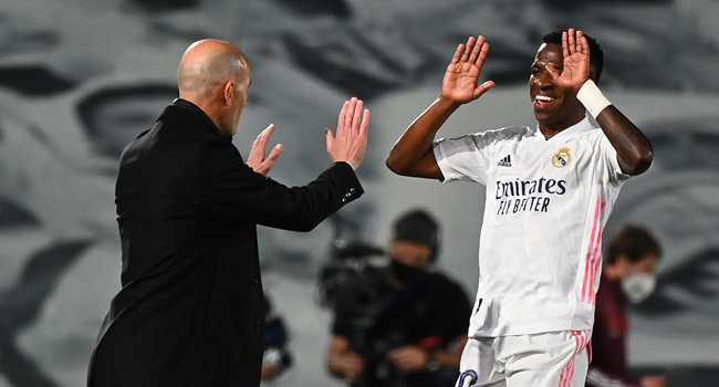 Real Madrid's Brazilian forward Vinicius Junior (R) celebrates with Real Madrid's French coach Zinedine Zidane after scoring a goal during the UEFA Champions League first leg quarter-final football match between Real Madrid and Liverpool at the Alfredo di Stefano stadium in Valdebebas in the outskirts of Madrid on April 6, 2021.  GABRIEL BOUYS / AFP