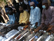 Bandit leaders stand before their surrendered guns on April 8, 2021 in Katsina State.