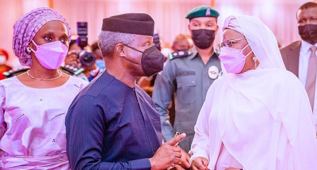 Vice President Yemi Osinbajo converses with First Lady Aisha Buhari during the launch ceremony of a book about the latter on April 8, 2021.