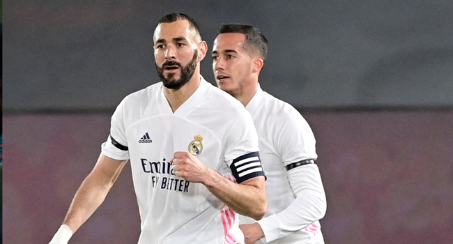 """Real Madrid's French forward Karim Benzema (L) celebrates after scoring next to Real Madrid's Spanish forward Lucas Vazquez during the """"El Clasico"""" Spanish League football match between Real Madrid CF and FC Barcelona at the Alfredo di Stefano stadium in Valdebebas, on the outskirts of Madrid on April 10, 2021. JAVIER SORIANO / AFP"""