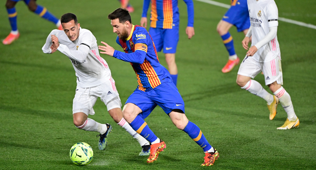 """Barcelona's Argentinian forward Lionel Messi (C) challenges Real Madrid's Spanish forward Lucas Vazquez during the """"El Clasico"""" Spanish League football match between Real Madrid CF and FC Barcelona at the Alfredo di Stefano stadium in Valdebebas, on the outskirts of Madrid on April 10, 2021. JAVIER SORIANO / AFP"""