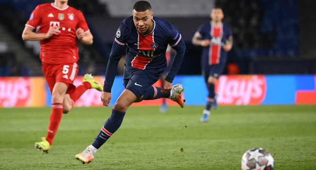 Paris Saint-Germain's French forward Kylian Mbappe (R) drives the ball during the UEFA Champions League quarter-final second leg football match between Paris Saint-Germain (PSG) and FC Bayern Munich at the Parc des Princes stadium in Paris, on April 13, 2021. FRANCK FIFE / AFP
