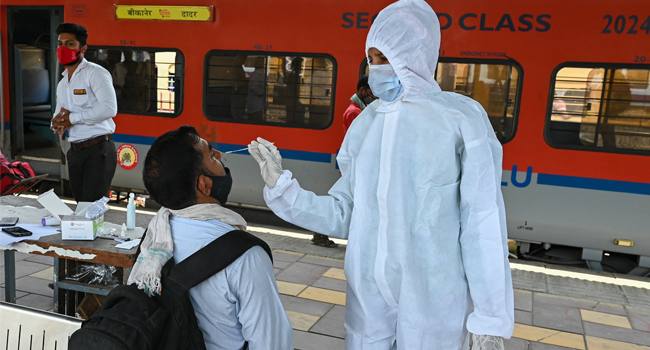 A health worker takes a nasal swab sample of a passenger for the Covid-19 coronavirus test after arriving at a railway platform on a long distance train, in Mumbai on April 14, 2021. Punit PARANJPE / AFP