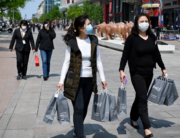 This file photo taken on April 17, 2020 shows two pedestrians carrying shopping bags along a street in Beijing. WANG ZHAO / AFP