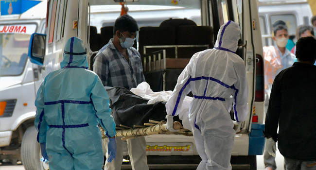 Family members, with help from the municipal staff transfer the bodies of the patients who died of the Covid-19 coronavirus disease from the ambulance at a crematorium in Bangalore on April 15, 2021. Manjunath Kiran / AFP