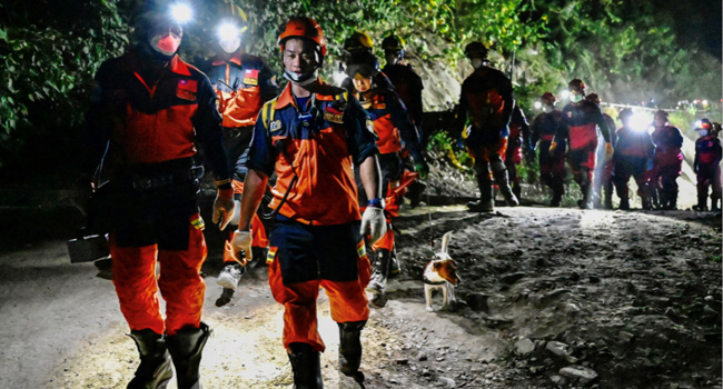Rescue workers walk at the site where a train derailed inside a tunnel in the mountains of Hualien eastern