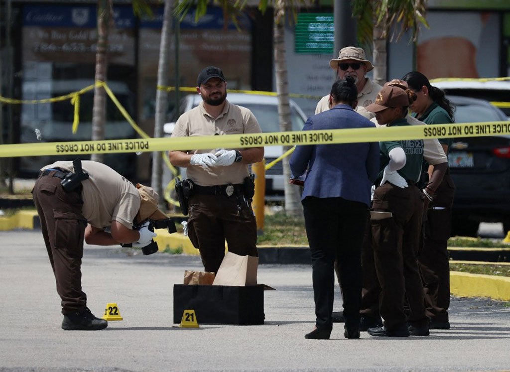 Miami-Dade police officers collect evidence near shell case evidence markers where a mass shooting took place outside of a banquet hall on May 30, 2021 in Hialeah, Florida.