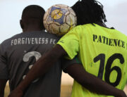 Two football team captains from Forgiveness FC (L) and from Patience FC (R) pose for a photo after playing a final peace football match with a line-up of teams made up of Christians and Muslims aimed at reuniting estranged neighbours in violent flashpoint within Jos, Plateau State, Nigeria, on May 14, 2021.