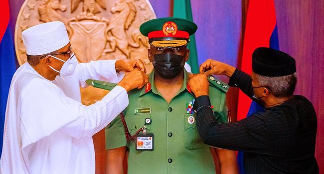 Lieutenant-General Ibrahim Attahiru (c) being decorated by President Muhammadu Buhari (L) and Vice President Yemi Osinbajo.