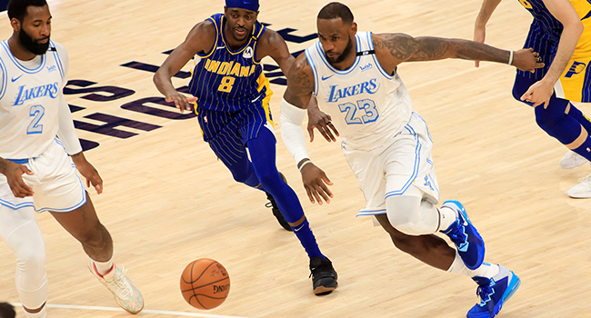 LeBron James #23 of the Los Angeles Lakers drives to the basket while guarded by Justin Holiday #8 of the Indiana Pacers during the fourth quarter at Bankers Life Fieldhouse on May 15, 2021 in Indianapolis, Indiana. Justin Casterline/Getty Images/AFP