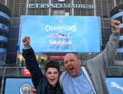 Manchester City fans, Ian Leonard and his son Jack celebrate winning the Premier League title outside the Etihad Stadium in Manchester, north west England, on May 11, 2021, after their closest challengers for the title Manchester United, lost to Leicester City this evening. Paul ELLIS / AFP