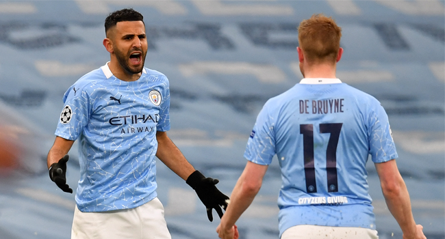 Manchester City's Algerian midfielder Riyad Mahrez (L) celebrates scoring the opening goal with Manchester City's Belgian midfielder Kevin De Bruyne during the UEFA Champions League second leg semi-final football match between Manchester City and Paris Saint-Germain (PSG) at the Etihad Stadium in Manchester, north west England, on May 4, 2021. Paul ELLIS / AFP