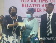 Chairman of the Lagos State Judicial Panel, Justice Doris Okuwobi, hands over a cheque to Bolanle Amudalat Kareem and her lawyer, Aderemi Aka on May 15, 2021.