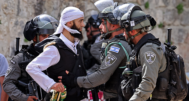 A Palestinian argues with Israeli security forces in Jerusalem's Old City on May 10, 2021, ahead of a planned march to commemorate Israel's takeover of Jerusalem in the 1967 Six-Day War. EMMANUEL DUNAND / AFP