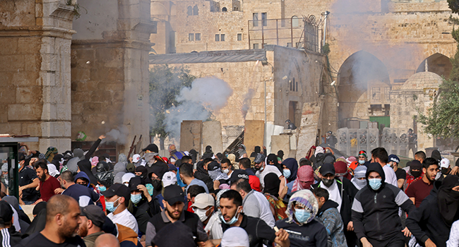 Palestinians run for cover from tear gas fired by Israeli security forces in Jerusalem's Old City on May 10, 2021, ahead of a planned march to commemorate Israel's takeover of Jerusalem in the 1967 Six-Day War. ahmad gharabli / AFP