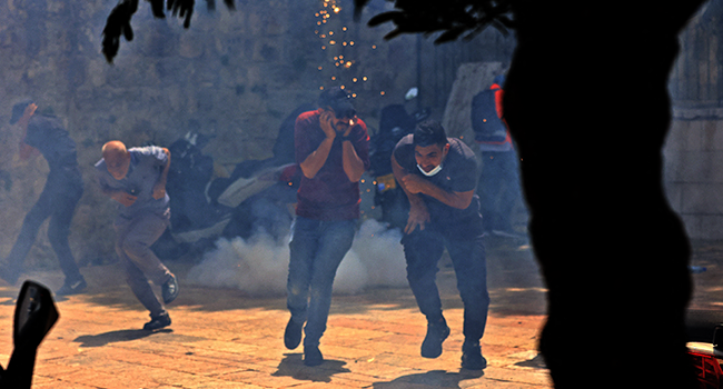 Palestinians run for cover from tear gas fired by Israeli security forces in Jerusalem's Old City on May 10, 2021, ahead of a planned march to commemorate Israel's takeover of Jerusalem in the 1967 Six-Day War. EMMANUEL DUNAND / AFP