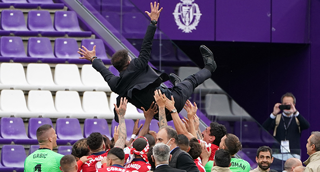 Atletico Madrid´s players toss Atletico Madrid's Argentine coach Diego Simeone after winning the Spanish league football match against Real Valladolid FC and the Liga Championship title at the Jose Zorilla stadium in Valladolid on May 22, 2021. CESAR MANSO / AFP