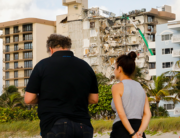 People observe the wreckage of a partially collapsed building in Surfside north of Miami Beach, Florida on June 25, 2021. Eva Marie UZCATEGUI / AFP