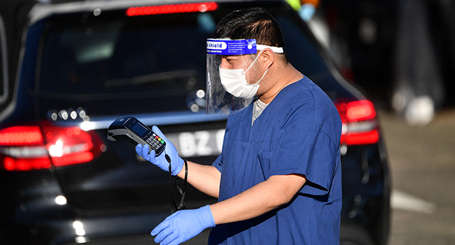 A health worker registers people for Covid-19 coronavirus tests at a drive-through testing centre at Bondi beach in Sydney on June 25, 2021, as authorities locked down several central areas of Australia's largest city to contain an outbreak of the highly contagious Delta variant. SAEED KHAN / AFP