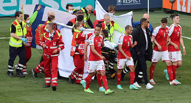 Denmark's players gather as paramedics attend to midfielder Christian Eriksen (not seen) during the UEFA EURO 2020 Group B football match between Denmark and Finland at the Parken Stadium in Copenhagen on June 12, 2021. WOLFGANG RATTAY / AFP / POOL