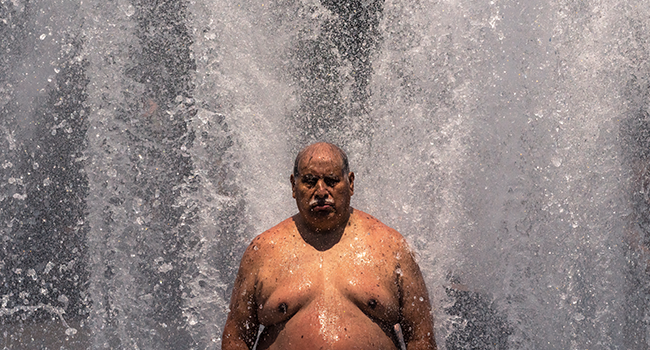 Pablo Miranda cools off in the Salmon Springs Fountain on June 27, 2021 in Portland, Oregon. Record breaking temperatures lingered over the Northwest during a historic heatwave this weekend. Nathan Howard/Getty Images/AFP