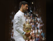 Serbia's Novak Djokovic speaks as he holds the winner's trophy after beating Italy's Matteo Berrettini during their men's singles final match on the thirteenth day of the 2021 Wimbledon Championships at The All England Tennis Club in Wimbledon, southwest London, on July 11, 2021. Adrian DENNIS / AFP