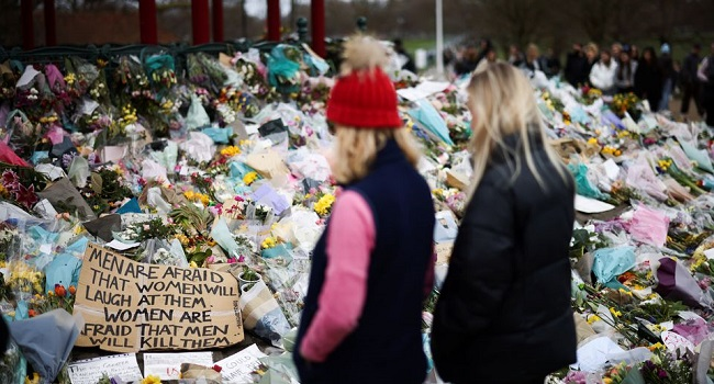 People observe a memorial site at the Clapham Common Bandstand following the kidnapping and murder of Sarah Everard in London Britain March 21 2021. REUTERS Henry Nicholls