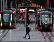 A man wearing a face mask walks towards tram station at Circular Quay in Sydney on July 19, 2021, amid a lockdown in Melbourne and Sydney as Australia seeks to contain a surge in coronavirus cases. Saeed KHAN / AFP