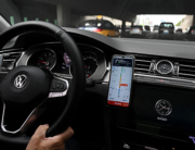 A driver uses the map on the Didi Chuxing ride-hailing app on his smartphone while driving on a street in Beijing on July 5, 2021. GREG BAKER / AFP