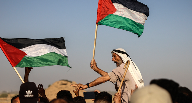 An elderly Palestinian man raises a national flag as youths shout slogans during a protest along the border fence, east of Khan Yunis in the southern Gaza Strip, on August 25, 2021. MAHMUD HAMS / AFP