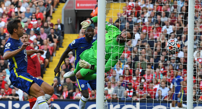 Liverpool's Brazilian goalkeeper Alisson Becker (C) cannot reach the ball as a header from Chelsea's German midfielder Kai Havertz (not pictured) opens the scoring in the English Premier League football match between Liverpool and Chelsea at Anfield in Liverpool, north west England on August 28, 2021. Paul ELLIS / AF