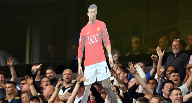 A cardboard cut out of new signing Cristiano Ronaldo is held by Manchester United supporters during the English Premier League football match between Wolverhampton Wanderers and Manchester United at the Molineux stadium in Wolverhampton, central England on August 29, 2021. Oli SCARFF / AFP