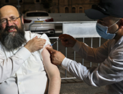 An Israeli health worker administers a third dose of the Pfizer-BioNtech Covid-19 vaccine to Jewish ultra-Orthodox man at a religious neighbourhood in Jerusalem on August 19, 2021. AHMAD GHARABLI / AFP