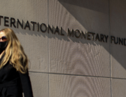 In this file photo taken on April 05, 2021, a woman walks past an International Monetary Fund headquarters (IMF) building in Washington, DC. MANDEL NGAN / AFP